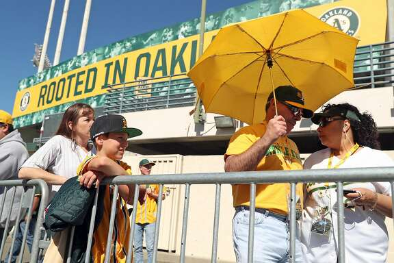 George and Marva DeCoite of Sacramento (right) and Patrick Flynn of Calistoga wait to enter Oakland Athletics' home opener at the Oakland Coliseum in Oakland, Calif., on Monday, April 3, 2017.