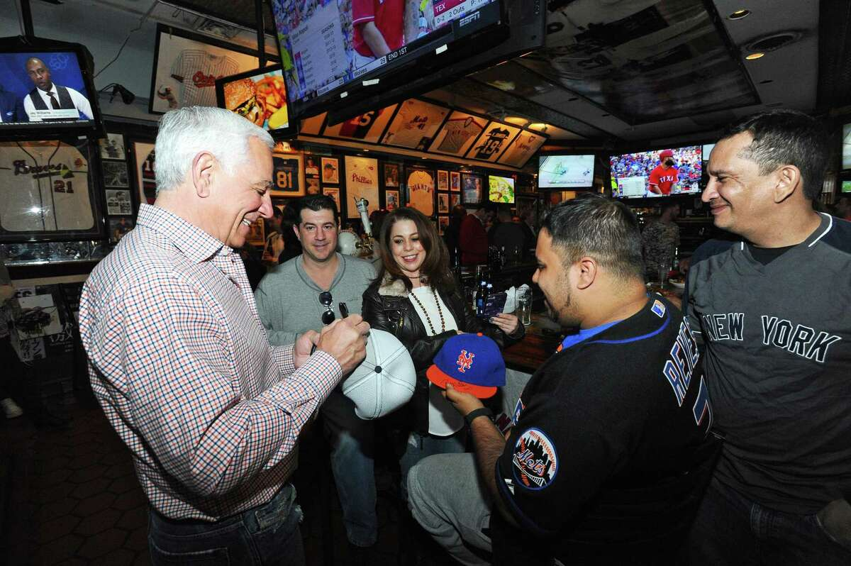 Above, Bobby Valentine signs baseball hats for customers inside Bobby Valentine's Sports Gallery Cafe during the bar's last night in downtown Stamford on Monday.