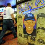 A Server Walks Past A Bobby Valentine Poster Inside Bobby Valentineu0027s  Sports Gallery Cafe In Downtown