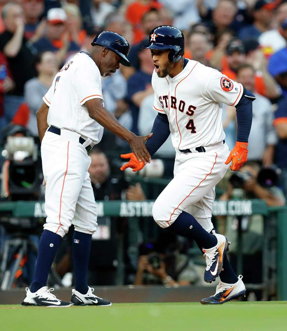 Houston Astros right fielder George Springer (4) celebrates his home run with third base coach Gary Pettis (8) in the first inning of the Houston Astros at Minute Maid Park, Friday, March 31, 2017, in Houston.