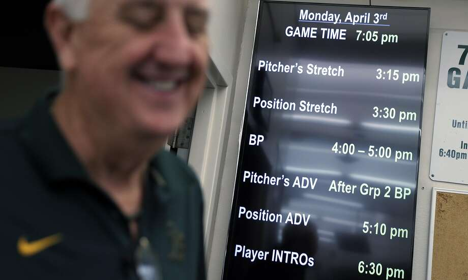 A digital screen behind Steve Vucinich, A's equipment manager, in the club house shows the opening day schedule for players at the Oakland Coliseum in Oakland, Calif., on Monday, April 3, 2017. Vucinich is entering his 50th season with the team, he started as a 15-year-old clubhouse attendant in 1968 when the A's first arrived in Oakland. Photo: Carlos Avila Gonzalez, The Chronicle