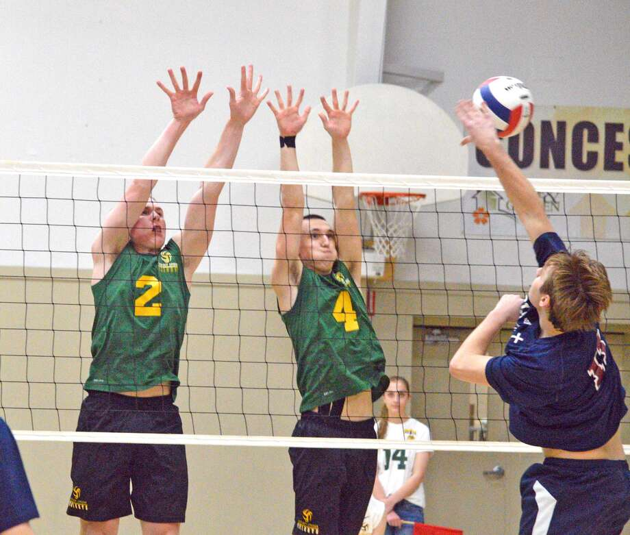 Metro-East Lutheran's Owen Gusewelle, left, and Thomas Schroader, middle, go up for a block during Monday's home match against Waterloo Gibault.