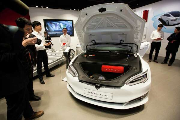 Members of the media check out a Tesla Model S 90D electric vehicle last month at the company's showroom in Hanam, South Korea. Tesla's value on Monday surpassed that of Ford Motor Co.