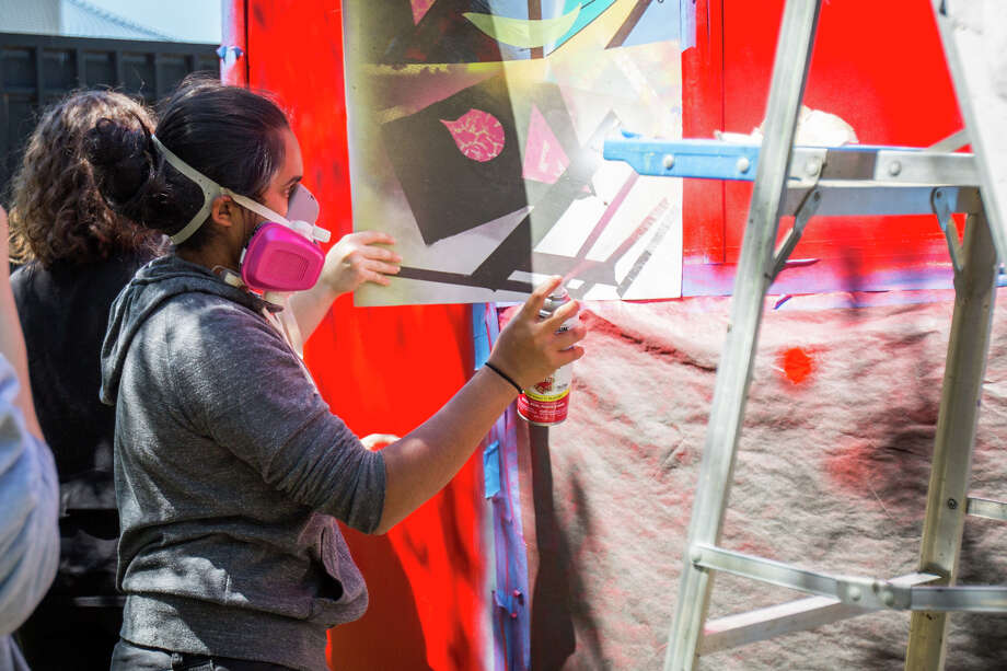 John Cooper School sophomore Divya Wagh spray paints a section of the PODS Art Project for The Woodlands Waterway Arts Festival on Monday. Photo: Michael Minasi, Staff Photographer / © 2017 Houston Chronicle