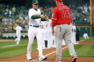Oakland Athletics' manager Bob Melvin shakes hands with Anaheim Angels' manager Mike Scioscia during A's home opener at the Oakland Coliseum in Oakland, Calif., on Monday, April 3, 2017.