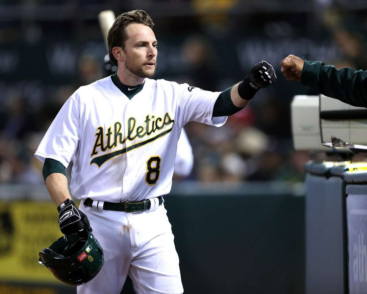 Oakland Athletics' Jed Lowrie scores on Yonder Alonso's RBI single in 5th inning against Anaheim Angels during A's home opener at the Oakland Coliseum in Oakland, Calif., on Monday, April 3, 2017.