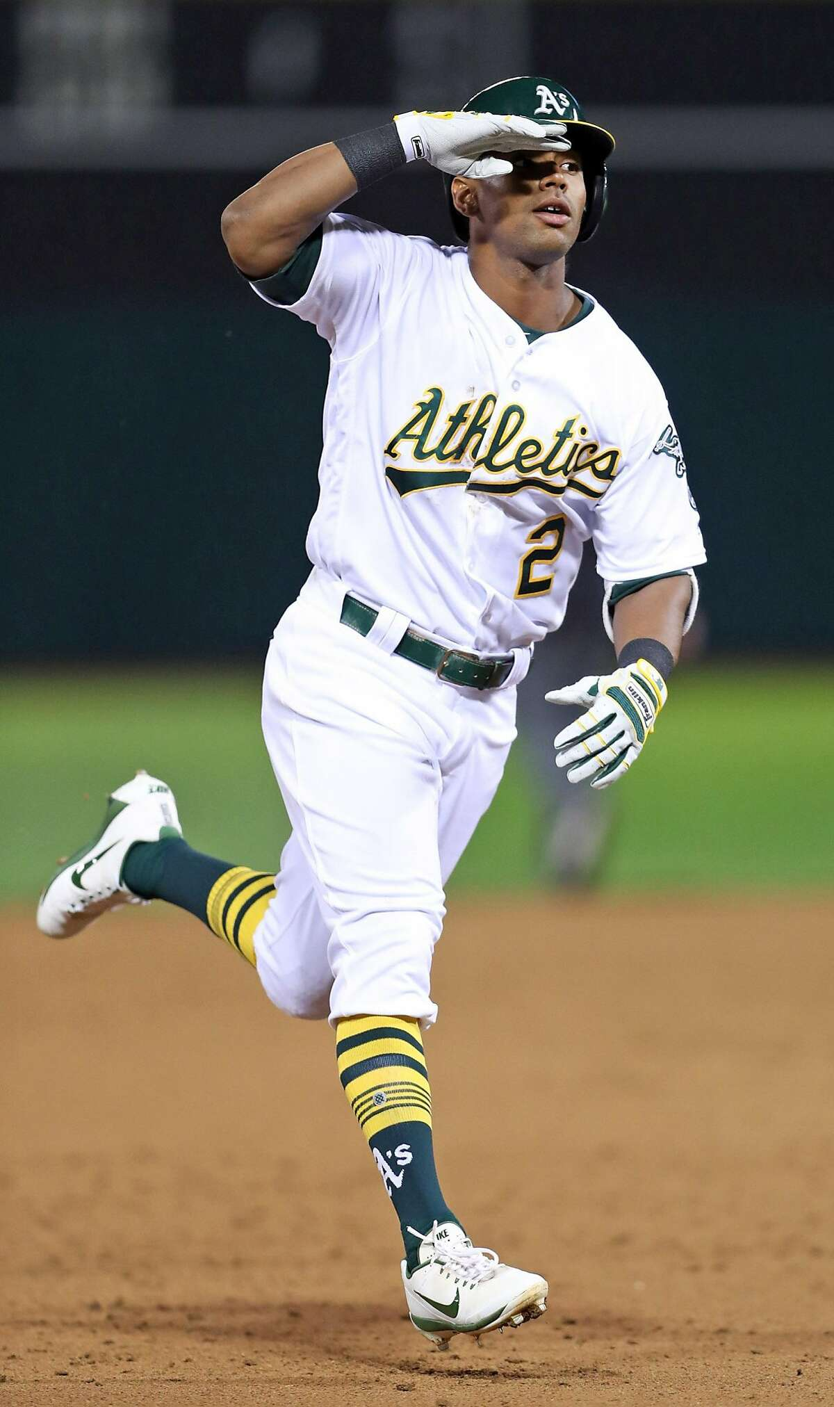 Oakland Athletics' Khris Davis salutes while rounding the bases after his 6th inning solo home run against Anaheim Angels during A's home opener at the Oakland Coliseum in Oakland, Calif., on Monday, April 3, 2017.