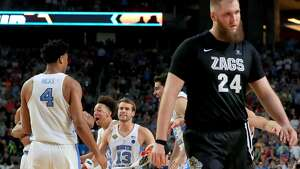 Przemek Karnowski #24 of the Gonzaga Bulldogs waks off the court as Isaiah Hicks #4, Kanler Coker #13, Shea Rush #11 and Luke Maye #32 of the North Carolina Tar Heels celebrate during the 2017 NCAA Men's Final Four National Championship game at University of Phoenix Stadium on April 3, 2017 in Glendale, Arizona. The Tar Heels defeated the Bulldogs 71-65. (Photo by Ronald Martinez/Getty Images)