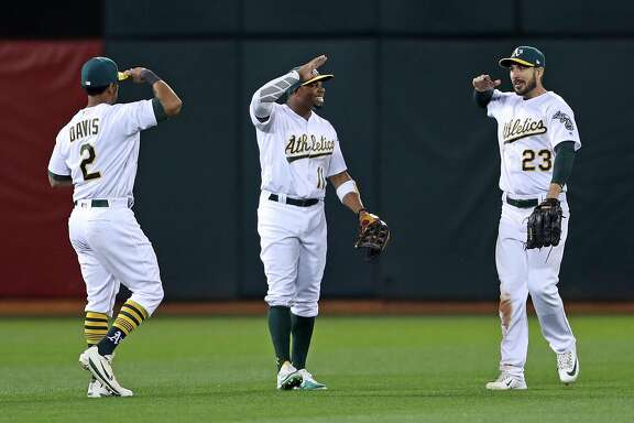 Oakland Athletics' Khris Davis, Rajai Davis and Matt Joyce salute each other in celebration of 4-2 win over Anaheim Angels in A's home opener at the Oakland Coliseum in Oakland, Calif., on Monday, April 3, 2017.