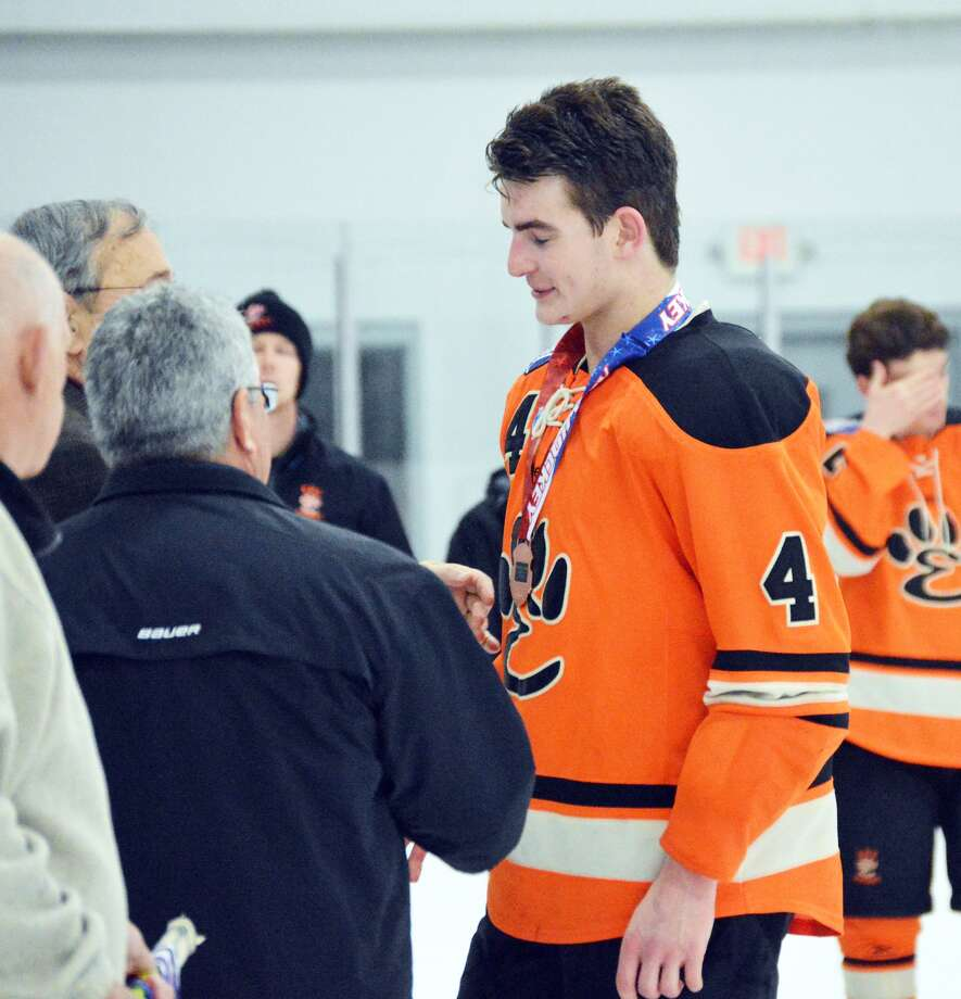 Edwardsville senior Jared Nosser, right, receives his bronze medal following the team's loss.