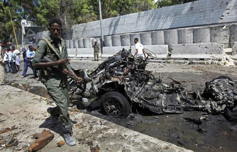 Somali soldiers walk near the wreckage of a car bomb in Mogadishu.  This week  President Donald Trump gave the U.S. military more authority to conduct offensive strikes on al-Qaida-linked militants. Photo: Farah Abdi Warsameh / Associated Press / Copyright 2017 The Associated Press. All rights reserved.