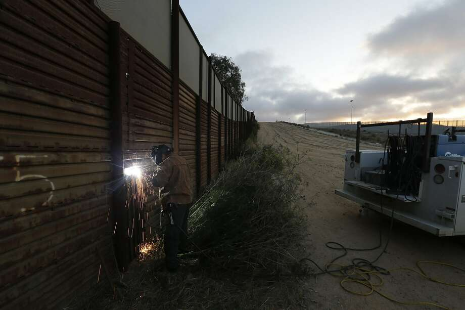 A U.S. Border Patrol agent works with a border wall repair crew in 2013 to weld a section of steel over a hole in San Diego. Photo: Gregory Bull, Associated Press