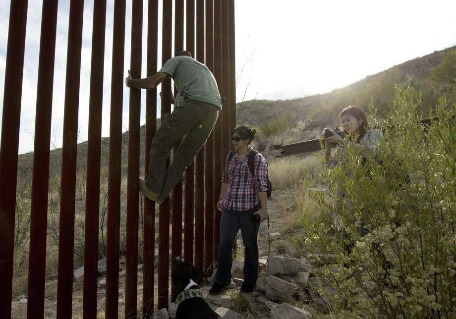Tim Foley shows how to climb a section of the border wall separating Mexico and the United States near where it ends as journalists Chitose Nakagawa (right) and Marcie Mieko Kagawa look on in Sasabe, Ariz., in this 2016 photo. Bids for the first border wall design contracts are due today. Photo: Associated Press /File Photo / Copyright 2017 The Associated Press. All rights reserved.