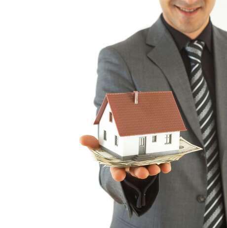 Man with outstreched hand holding money and a house. Real estate. Photo: STOCK XPERT