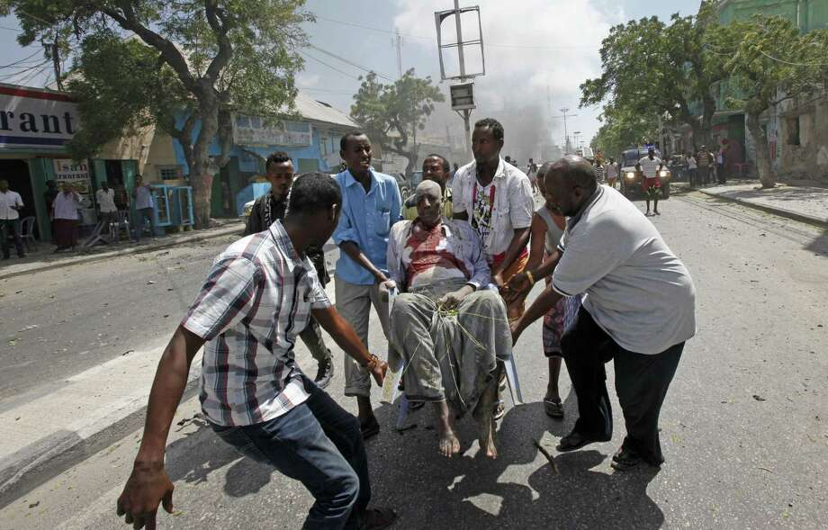 Rescuers carry away a man who was wounded in a car bomb attack in Mogadishu, Somalia Monday, March 13, 2017. A suicide car bomber detonated near the Weheliye hotel in the capital Monday morning, killing a number of people on the busy Maka Almukarramah road, police said. (AP Photo/Farah Abdi Warsameh) Photo: Farah Abdi Warsameh, STR / Associated Press / Copyright 2017 The Associated Press. All rights reserved.