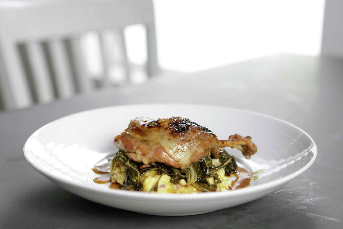 Duck leg confit with corn pudding, belly bacon collards and cane vinegar gastrique at Field & Tides
