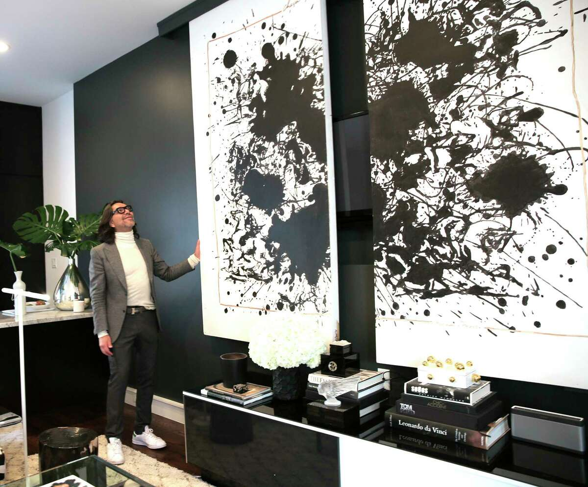 Cerón shows off their hidden television behind a painting that used to be a window display at Hermes.