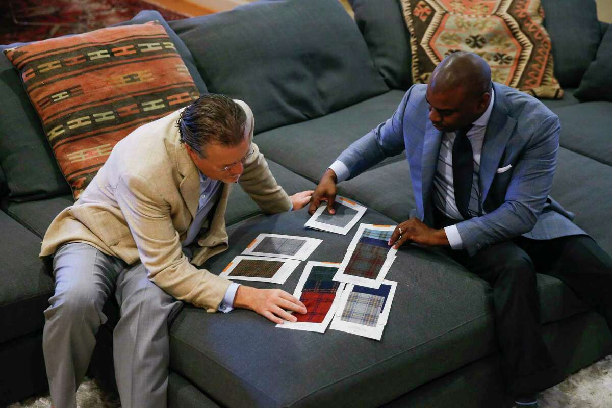 Established Bespoke owner Gary Warfield, right, and client Kevin Jones, left, look through fabric samples on Jones' couch Saturday, Dec. 31, 2016 in Houston. Warfield's company makes house calls to fit clients clothes. ( Michael Ciaglo / Houston Chronicle )