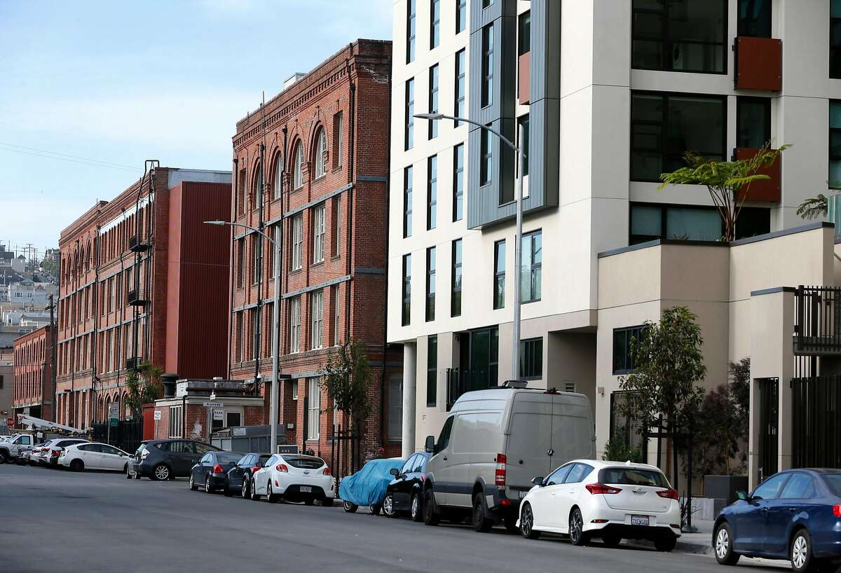 At right, the One Henry Adams apartment complex at Division and Henry Adams streets dwarfs older brick warehouses in San Francisco, Calif. on Tuesday, April 4, 2017.