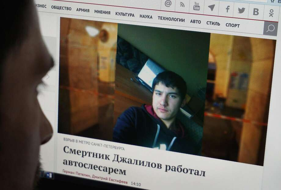 A Moscow resident looks at a news report with a photograph of Kyrgyz-born Russian citizen, Akbarzhon Dzhalilov, who is a suspect in the subway blast. Photo: -, AFP/Getty Images