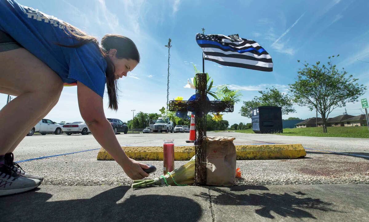 Natasha Lewis leaves a painted rock at the memorial for Harris County Precinct 3 Assistant Chief Deputy Clinton Greenwood outside the Baytown Courthouse Tuesday, April 4, 2017, in Baytown, Texas. Greenwood was fatally shot as he arrived to work Monday morning.