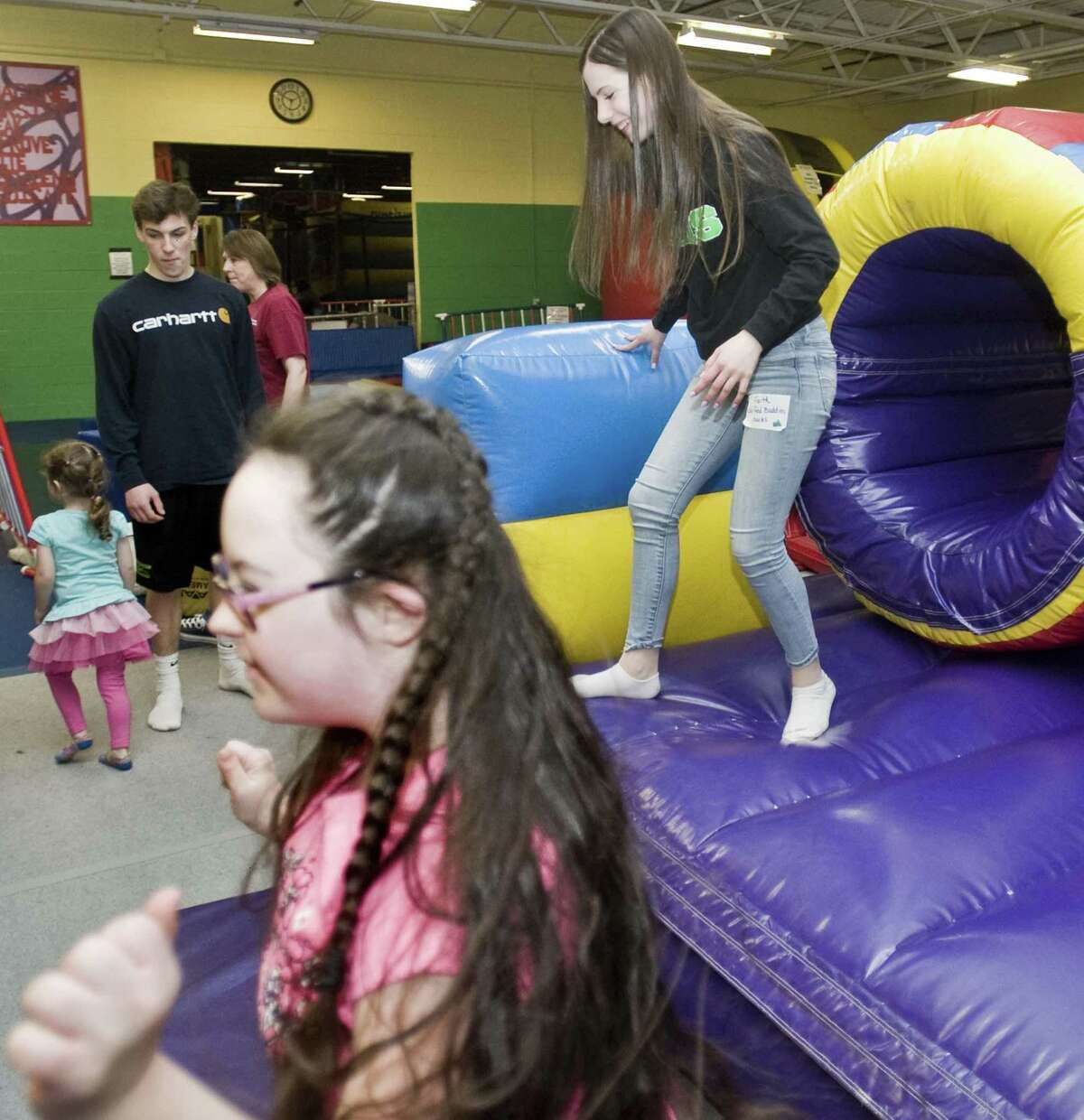Kally Trudeau, 13 of New Milford, comes out of the Obstacle Course at the Children's Movement Center with New Milford High School sophomore Faith Rosenhagen, right, as part of the high school's Unified Buddies program. Monday, April 3, 2017