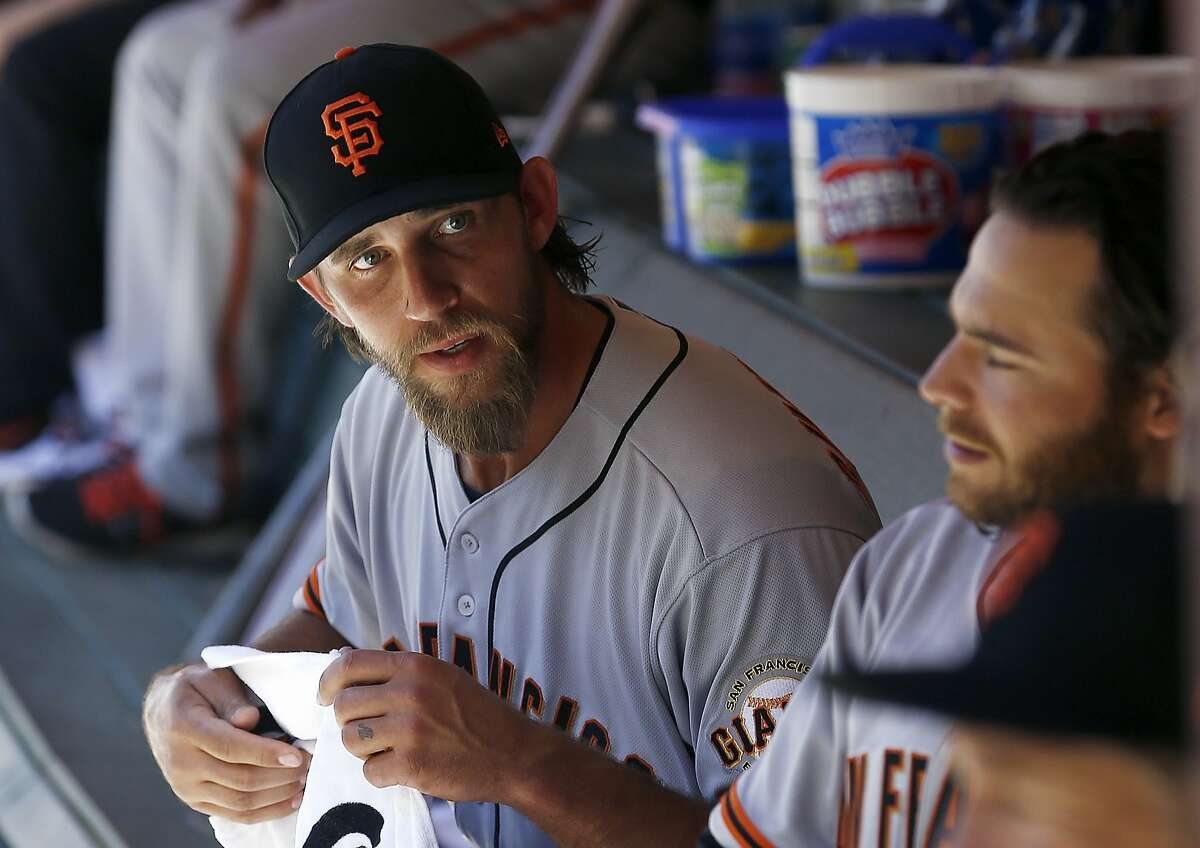 San Francisco Giants' Madison Bumgarner, left, talks with Brandon Crawford, right, in the dugout during the seventh inning of an Opening Day baseball game against the Arizona Diamondbacks Sunday, April 2, 2017, in Phoenix. (AP Photo/Ross D. Franklin)