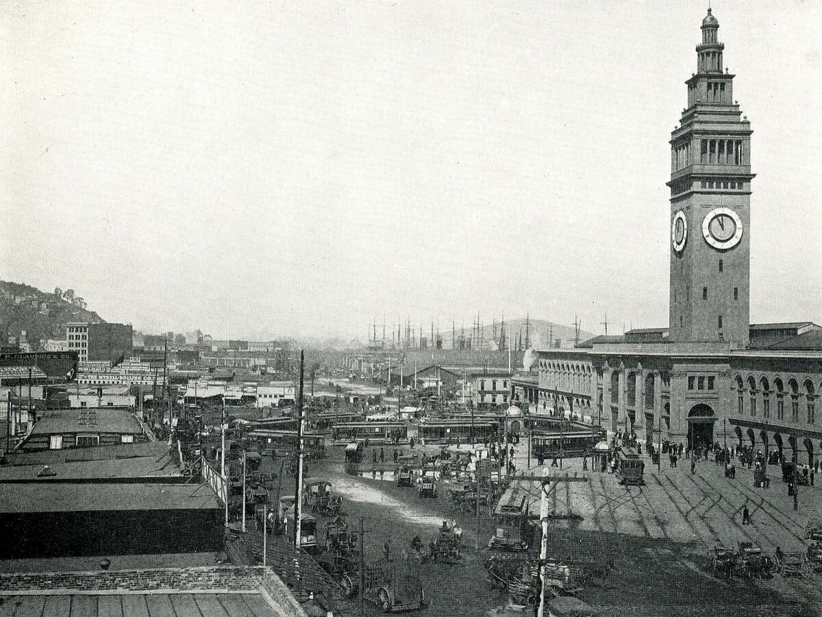 View of East Street, showing the Street Car Loop in front of the Ferry Building. Telegraph Hill is on the left.
