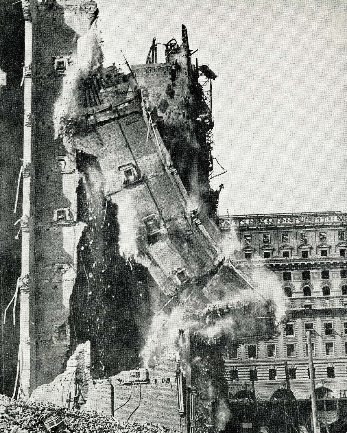 Razing the walls of the old Palace Hotel, one of the most spectacular photographs taken during the rebuilding of San Francisco. These walls were pulled down with wire cables operated by donkey engine.