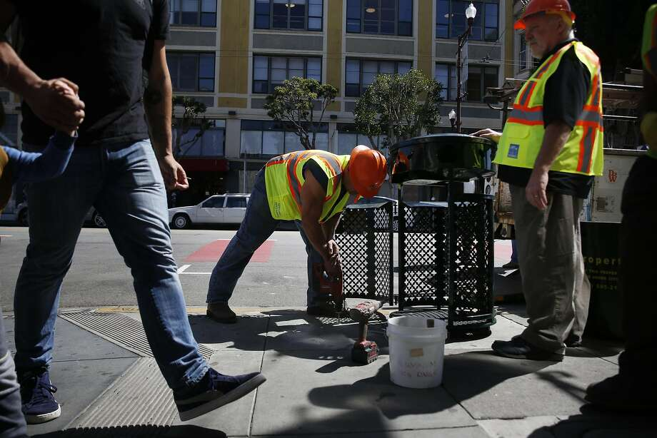"""Department of Public Works employee Tony Thomas helps install a new trash can on Mission Street. The city's """"Yes We Can"""" initiative will about double the number of trash bins along a stretch of Mission. Photo: Lea Suzuki, The Chronicle"""