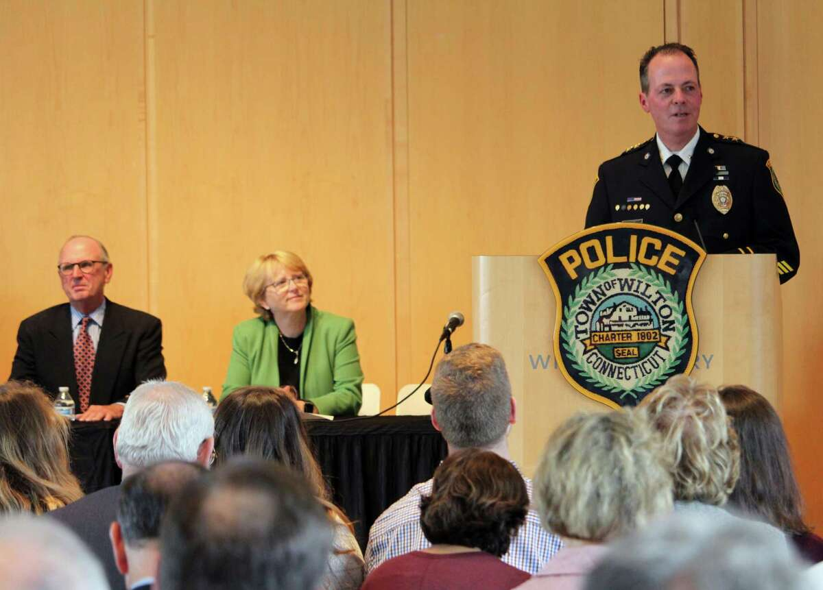 John Lynch giving a speech at his swearing-in ceremony for Wilton Police Chief on Wednesday, with Police Commission Chairman Donald Sauvigne and First Selectman Lynne Vanderslice sitting to his left.