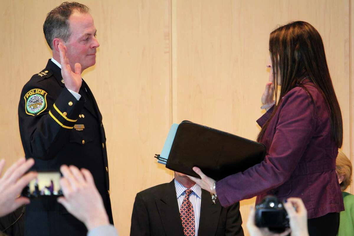 John Lynch being sworn in by Town Clerk Lori Kaback as the new Wilton Police Chief on Wednesday.