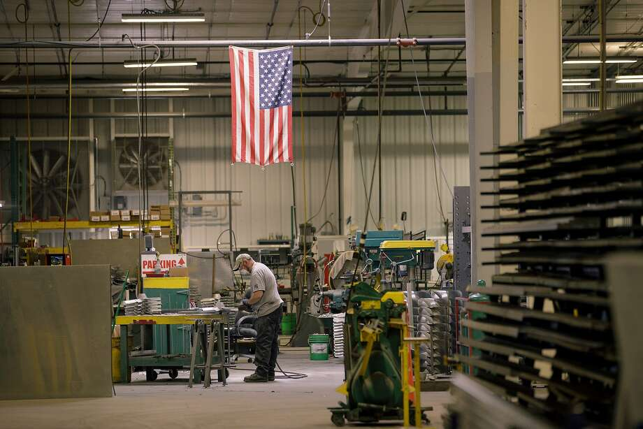 An employee grinds ventilator blades while standing underneath an American flag at the Super Vac Manufacturing Co. production facility in Fort Collins, Colo. Photo: Matthew Staver, Bloomberg