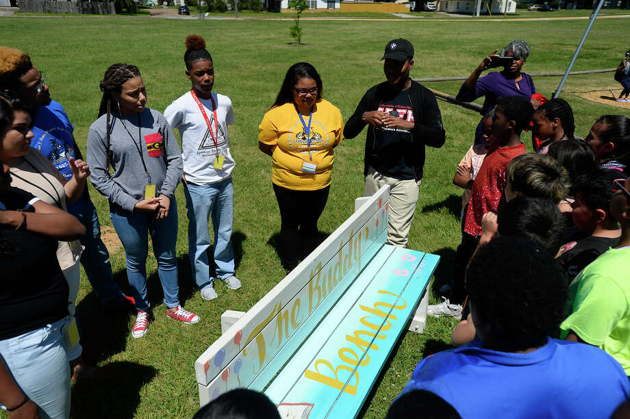 Ozen High School students from Youth Leadership Southeast Texas talk with fourth graders about a new buddy bench on the playground at Jones-Clark Elementary School on Tuesday. The bench will give students a place to sit and find new friends when they don't have anyone to play with. Photo taken Tuesday 4/4/17 Ryan Pelham/The Enterprise Photo: Ryan Pelham / ©2017 The Beaumont Enterprise/Ryan Pelham