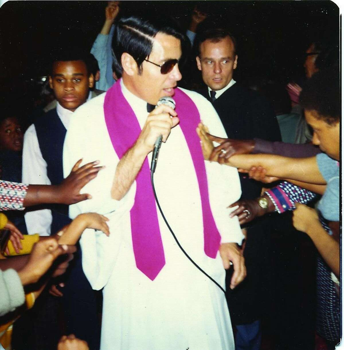 Jim Jones in white robe and sunglasses being touched by members of the Peoples Temple in Los Angeles in 1974.