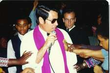 Jim Jones in white robe and sunglasses being touched by members of the Peoples Temple in Los Angeles, CA in 1974.
