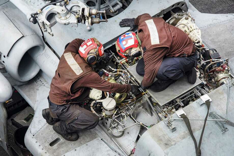 Navy Seaman Tri Lee, left, and Petty Officer 2nd Class Andres Guevara perform maintenance in February 2017 on a Sikorsky Aircraft MH-60 Sea Hawk helicopter on the flight deck of the aircraft carrier USS Carl Vinson in the Pacific Ocean, Feb. 9, 2017. (Navy photo by Petty Officer 2nd Class Sean M. Castellano) Photo: MC2 Sean Castellano