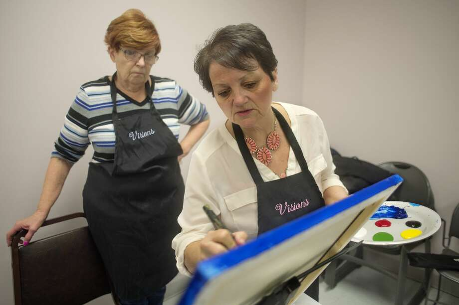 Visions by Vicki founder Vicki Thomas shows Susan Klich, of Midland how to blend her paint during a two hour painting class at Trailside Senior Center Thursday morning. Thomas teaches all ages in two hour sessions and has created more than 100 different paintings. Photo: Brittney Lohmiller/Midland Daily News