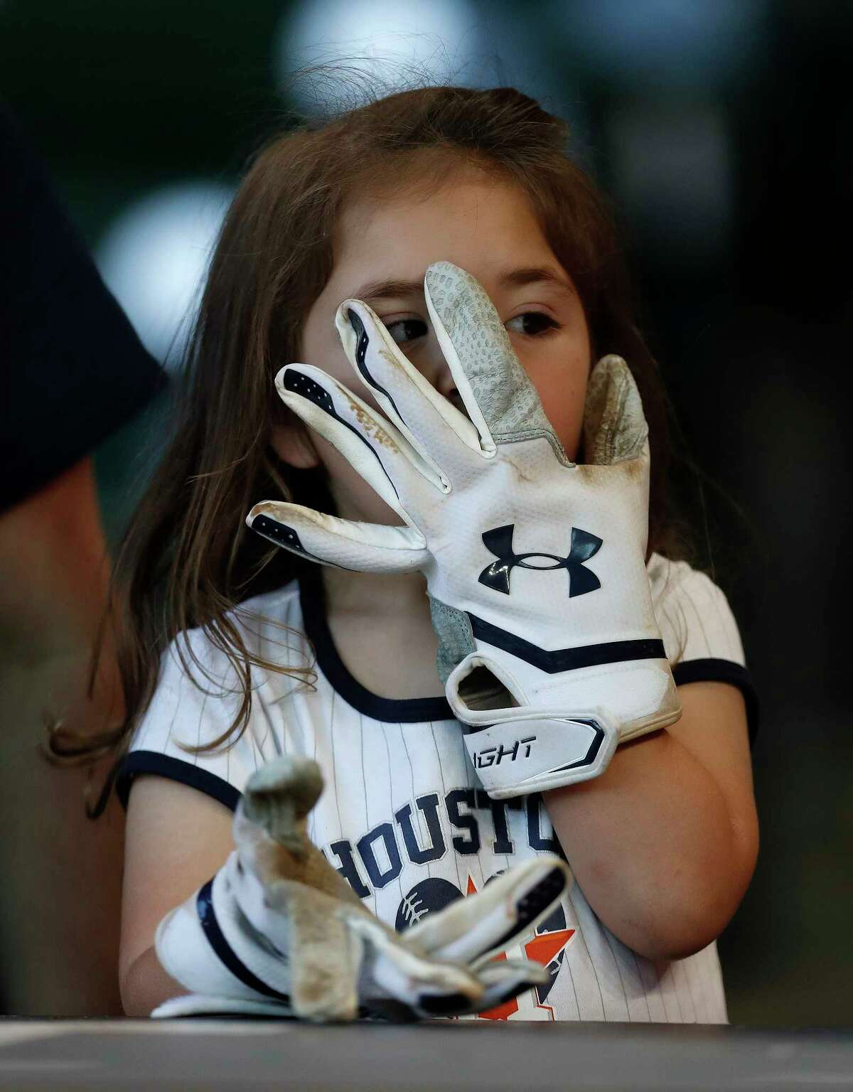 Lilliana Cardoza, 3, wears a pair of batting gloves given to her by Astros catcher Brian McCann during batting practice before the start of an MLB baseball game at Minute Maid Park, Tuesday, April 4, 2017, in Houston.