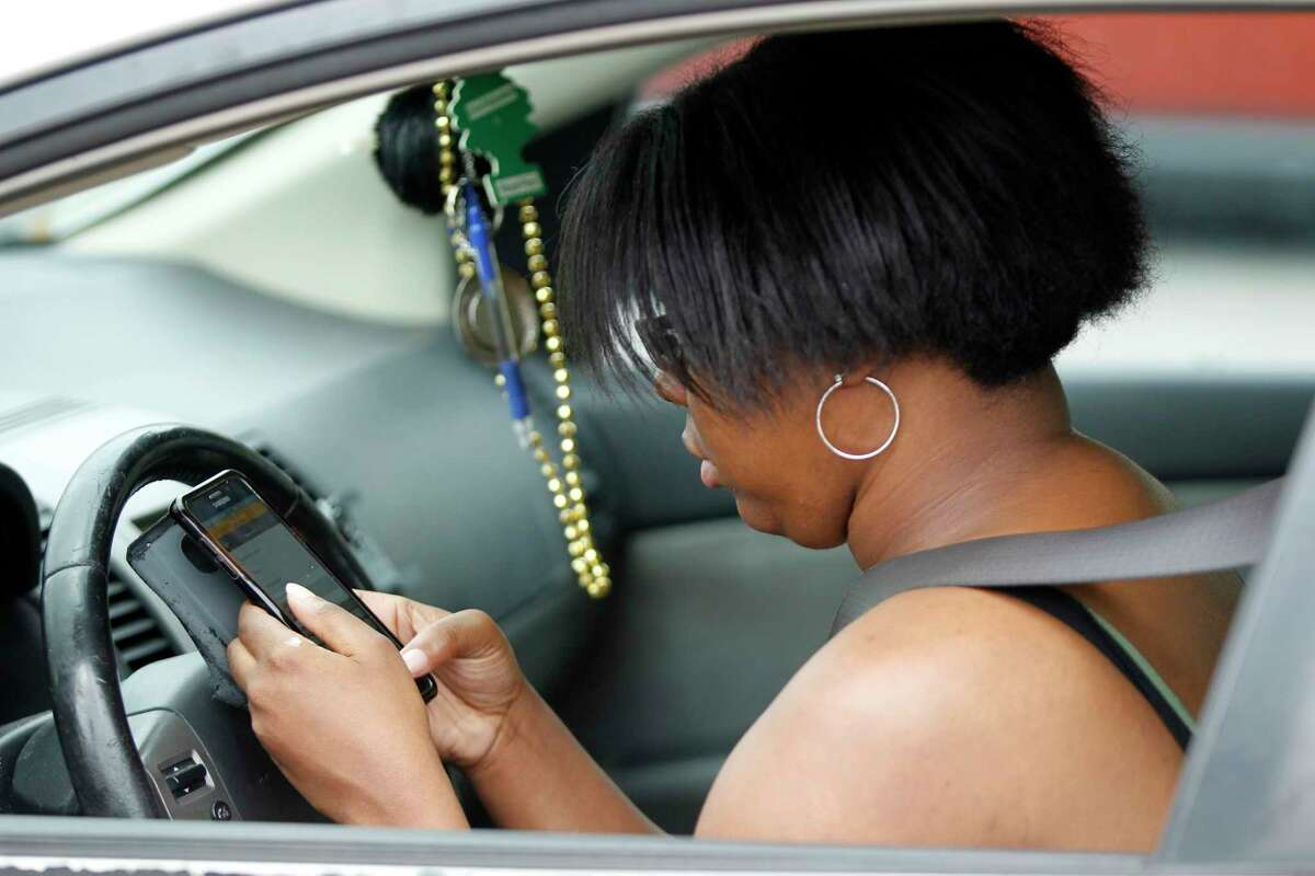 A woman texts as she drives along Westheimer near The Galleria in Houston on March 9.