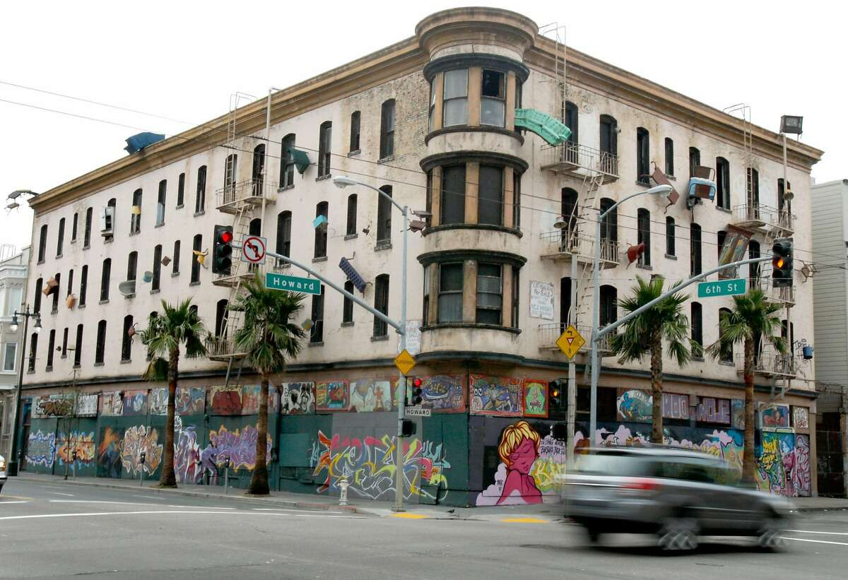 A motorist drives past the old Hugo Hotel, now known as the Defenestration Building, at Sixth and Howard Streets in San Francisco, Calif. on Saturday, Jan. 26, 2008. A plan in the works may mean the building and an art project by artist Brian Goggin could be razed to make way for new development. Goggin's 1997 project, which literally means