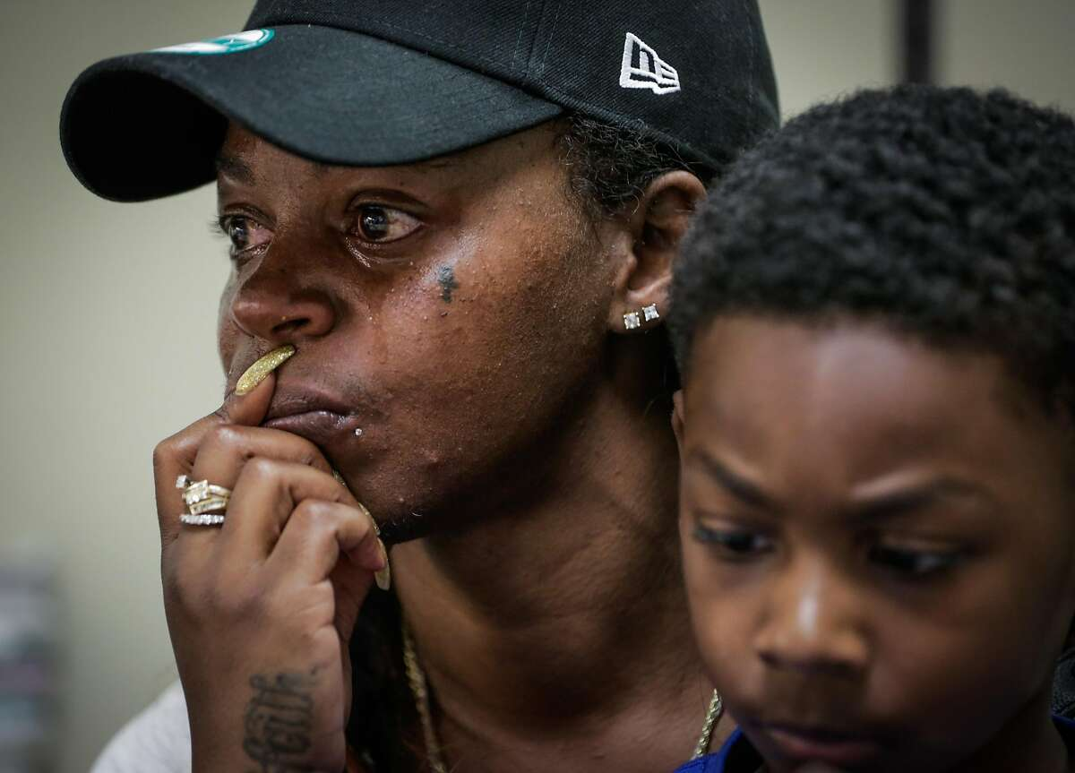 Displaced resident Kim Usher gets emotional while talking to a housing counselor with the city of Oakland at a local assistance center regarding her options for housing after losing her home in a fire on San Pablo Avenue last week in Oakland, California, on Tuesday, April 4, 2017. Usher lives with her mother and three sons and has one more night to stay at the West Oakland Youth Center. Her son Million Smith, 8 (right) is pictured.