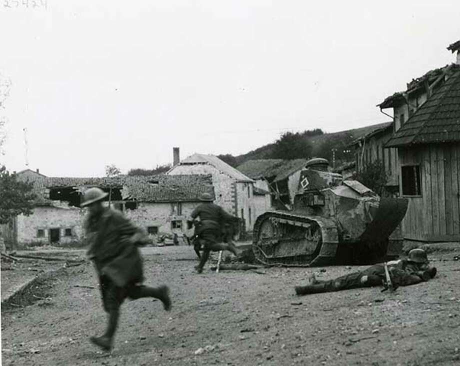 "Original caption: ""18th Infantry Regiment under fire in Exermont, France. A French tank and dead German solder are in the street."" Oct. 7, 1918 Photo: Courtesy U.S. Army Heritage And Education Center"