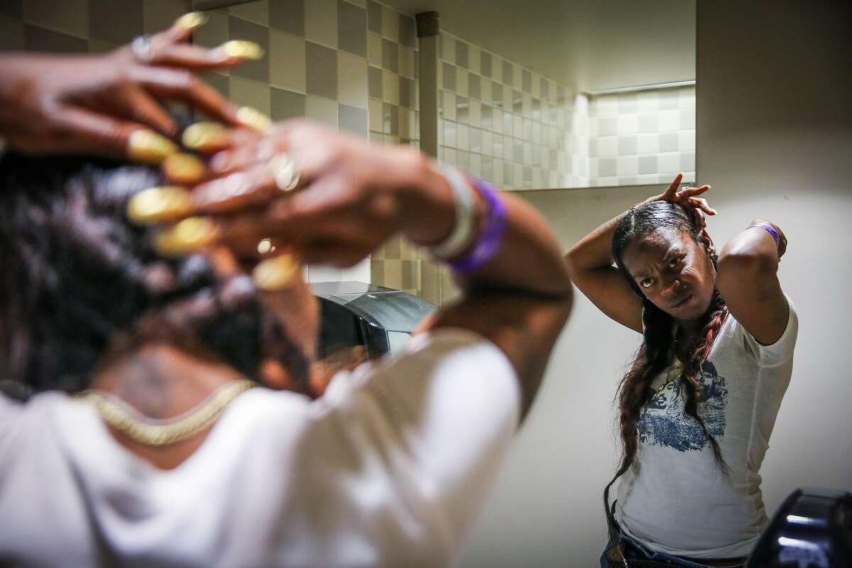 Displaced resident Kim Usher does her hair in the restroom before getting a replacement identification card at a local assistance center after losing her home in a fire on San Pablo Avenue last week in Oakland, California, on Tuesday, April 4, 2017. Kim lives with her mother Roberta Williamsand three sons. She has one more night to stay at the West Oakland Youth Center.