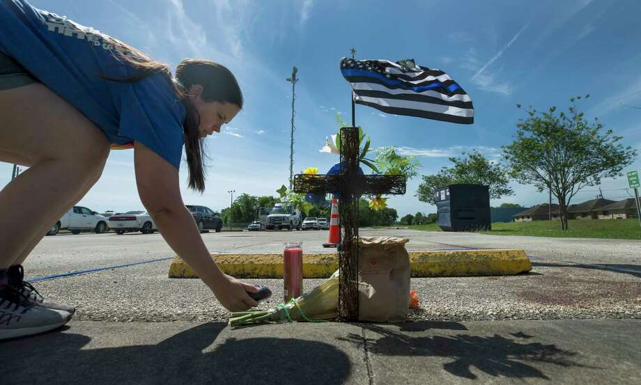 Natasha Lewis leaves a painted rock at the memorial for Harris County Precinct 3 Assistant Chief Deputy Clinton Greenwood outside the Baytown Courthouse Tuesday, April 4, 2017, in Baytown, Texas. Greenwood was fatally shot as he arrived to work Monday morning. ( Godofredo A. Vasquez / Houston Chronicle ) Photo: Godofredo A. Vasquez, Staff / Godofredo A. Vasquez
