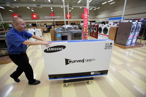 Bryan Jones of Conn's wheels a television out to a customer in Baytown. Conn's shares rose Tuesday.
