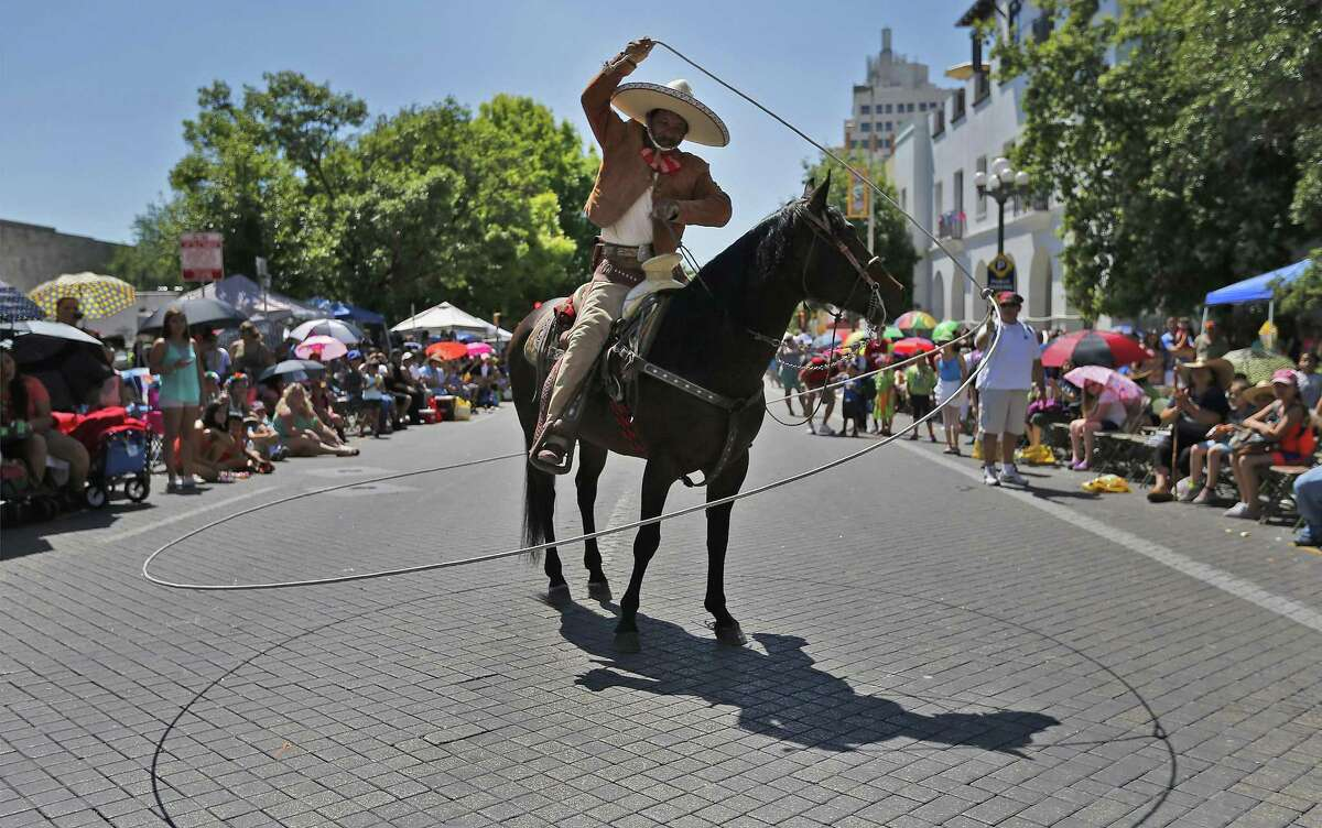 A caballero twirls his lasso while performing for the crowd of parade watchers during the 2016 Battle of Flowers parade on April 22, 2016.