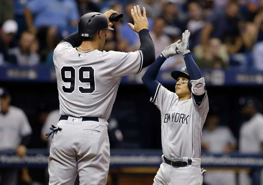 New York Yankees' Ronald Torreyes, right, high fives Aaron Judge after Torreyes hit a two-run home run off Tampa Bay Rays starting pitcher Jake Odorizzi during the third inning of a baseball game Tuesday, April 4, 2017, in St. Petersburg, Fla. (AP Photo/Chris O'Meara) ORG XMIT: SPD109 Photo: Chris O'Meara / Copyright 2017 The Associated Press. All rights reserved.