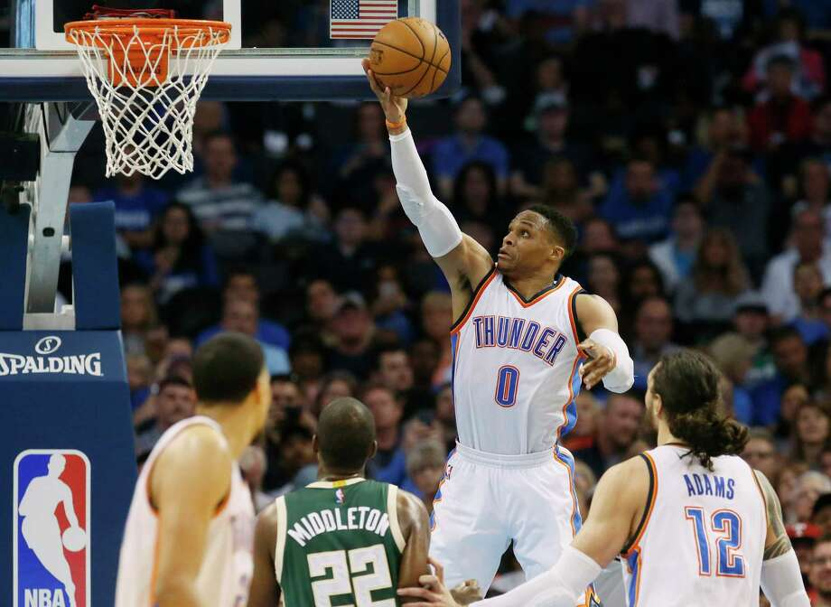 Oklahoma City Thunder guard Russell Westbrook (0) shoots in front of Milwaukee Bucks guard Khris Middleton (22) and teammates Andre Roberson, left, and Steven Adams (12) in the second quarter of an NBA basketball game in Oklahoma City, Tuesday, April 4, 2017. (AP Photo/Sue Ogrocki) ORG XMIT: OKSO104 Photo: Sue Ogrocki / AP2017