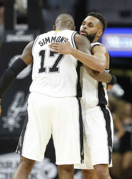 Spurs' Patty Mills (08) gets a hug from teammate Jonathon Simmons (17) after hitting a three-pointer in overtime against the Memphis Grizzlies during their game at the AT&T Center on Tuesday, Apr. 4, 2017. Spurs defeated the Grizzlies in overtime, 95-89. (Kin Man Hui/San Antonio Express-News) Photo: Kin Man Hui, Staff / San Antonio Express-News / ©2017 San Antonio Express-News